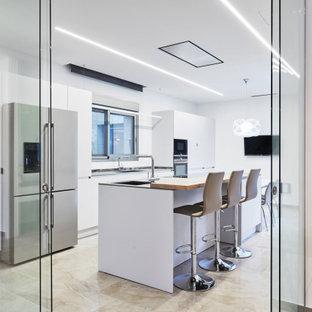 Imagen de cocina de galera, contemporánea, cerrada, con armarios con paneles lisos, puertas de armario blancas, electrodomésticos de acero inoxidable, una isla, suelo beige y encimeras grises