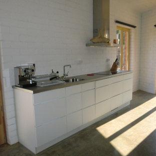 バルセロナの大きいインダストリアルスタイルのおしゃれなキッチン (シングルシンク、シェーカースタイル扉のキャビネット、白いキャビネット、ステンレスカウンター、白い調理設備、コンクリートの床) の写真