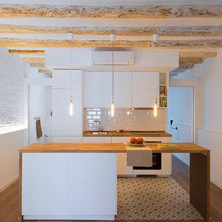 Idéer för att renovera ett litet funkis linjärt kök med öppen planlösning, med en enkel diskho, släta luckor, vita skåp, träbänkskiva, vitt stänkskydd, stänkskydd i tunnelbanekakel, integrerade vitvaror, cementgolv, en köksö och vitt golv