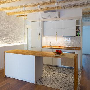 バルセロナの小さいコンテンポラリースタイルのおしゃれなキッチン (シングルシンク、フラットパネル扉のキャビネット、白いキャビネット、木材カウンター、白いキッチンパネル、サブウェイタイルのキッチンパネル、白い調理設備、無垢フローリング、茶色い床) の写真