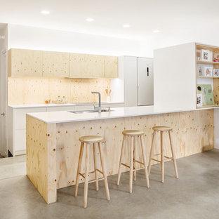 Diseño de cocina escandinava con fregadero bajoencimera, armarios con paneles lisos, puertas de armario de madera clara, salpicadero de madera, suelo de cemento, península, suelo gris y encimeras blancas