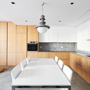 Imagen de cocina en L, contemporánea, abierta, con armarios con paneles lisos, puertas de armario de madera oscura, salpicadero verde, suelo gris, encimeras grises y fregadero bajoencimera