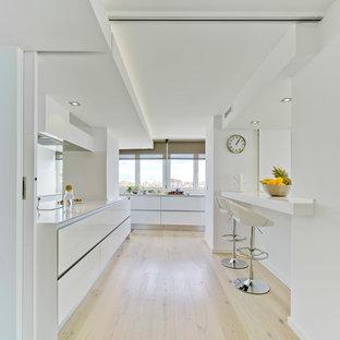 Modelo de cocina lineal, actual, grande, abierta, sin isla, con armarios con paneles lisos, puertas de armario blancas, encimera de cuarzo compacto, suelo de madera clara y suelo beige