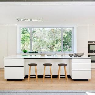 Imagen de cocina lineal, actual, grande, con armarios con paneles lisos, puertas de armario blancas, encimera de cuarzo compacto, suelo de madera en tonos medios, una isla y suelo beige
