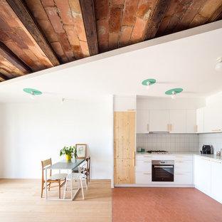 Modelo de cocina comedor en L, escandinava, de tamaño medio, sin isla, con armarios con paneles lisos, puertas de armario blancas, salpicadero de azulejos de cerámica y electrodomésticos de acero inoxidable