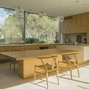 Ejemplo de cocina en L, moderna, con armarios con paneles lisos, puertas de armario de madera clara, una isla, suelo beige, fregadero bajoencimera, encimera de cemento, salpicadero de vidrio, electrodomésticos con paneles y encimeras grises