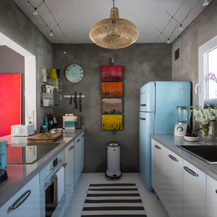 Inspiration for a small eclectic galley separate kitchen in Malaga with a drop-in sink, grey splashback, no island, flat-panel cabinets, white cabinets, solid surface benchtops, ceramic floors, coloured appliances and grey benchtop.