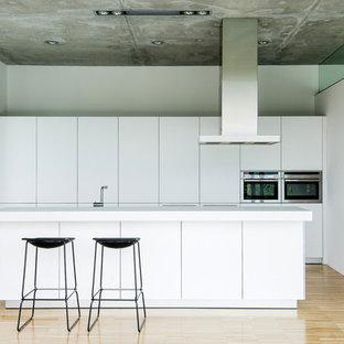 Ejemplo de cocina minimalista con armarios con paneles lisos, puertas de armario blancas, electrodomésticos de acero inoxidable, una isla, suelo beige y encimeras blancas