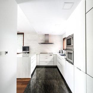 Foto de cocina en U, contemporánea, de tamaño medio, abierta, con fregadero de un seno, armarios con paneles lisos, puertas de armario blancas, salpicadero blanco, electrodomésticos de acero inoxidable y península