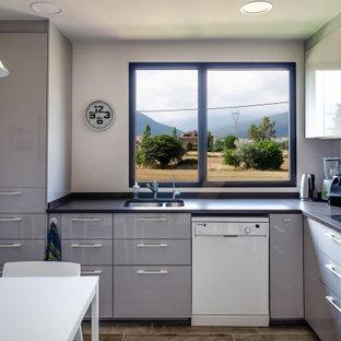 Diseño de cocina en L, actual, pequeña, sin isla, con fregadero de doble seno, armarios con paneles lisos, puertas de armario grises, salpicadero negro, suelo gris y encimeras negras