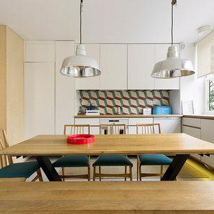 Modelo de cocina comedor en L, escandinava, sin isla, con armarios con paneles lisos, puertas de armario blancas, salpicadero multicolor, electrodomésticos blancos y suelo gris