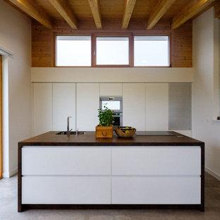 Modelo de cocina actual con fregadero bajoencimera, armarios con paneles lisos, puertas de armario blancas, encimera de madera, electrodomésticos de acero inoxidable, suelo de cemento, una isla y suelo gris