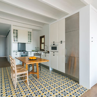 This is an example of a mid-sized scandinavian l-shaped eat-in kitchen in Barcelona with a farmhouse sink, beige cabinets, stainless steel appliances, white splashback, ceramic floors and no island.