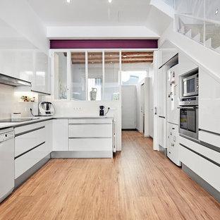 Diseño de cocina en U, contemporánea, cerrada, sin isla, con armarios con paneles lisos, puertas de armario blancas, salpicadero beige, electrodomésticos blancos, suelo de madera en tonos medios, suelo beige y encimeras blancas