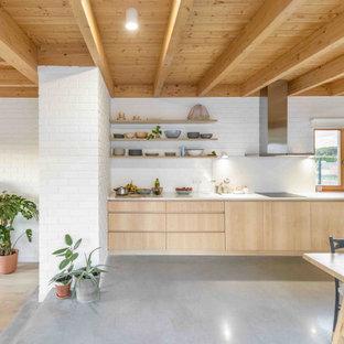 На фото: большая прямая кухня в современном стиле с обеденным столом, монолитной раковиной, плоскими фасадами, светлыми деревянными фасадами, белым фартуком, фартуком из кирпича, техникой из нержавеющей стали, серым полом, белой столешницей и деревянным потолком