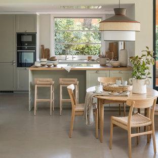 Foto de cocina comedor mediterránea, de tamaño medio, con puertas de armario grises, encimera de madera, suelo de cemento, península, suelo gris, fregadero bajoencimera, armarios estilo shaker y electrodomésticos negros