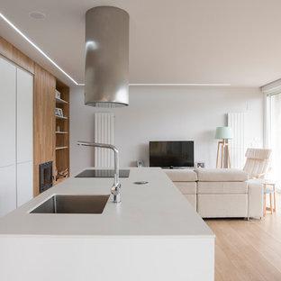 Diseño de cocina de galera, actual, abierta, con armarios con paneles lisos, puertas de armario blancas, electrodomésticos de acero inoxidable, una isla, encimeras blancas, fregadero bajoencimera, suelo de madera clara y suelo beige