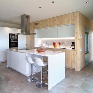 Foto de cocina costera con fregadero de un seno, armarios con paneles lisos, puertas de armario blancas, salpicadero blanco, electrodomésticos negros, una isla, suelo gris y encimeras blancas
