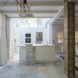 Imagen de cocina lineal, actual, con armarios con paneles lisos, puertas de armario blancas, electrodomésticos de acero inoxidable, suelo de mármol, una isla, suelo blanco, encimeras blancas y fregadero bajoencimera