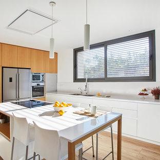 Foto de cocina minimalista con armarios con paneles lisos, puertas de armario blancas, encimera de cuarzo compacto, salpicadero blanco, electrodomésticos de acero inoxidable, suelo de madera en tonos medios, una isla y encimeras blancas