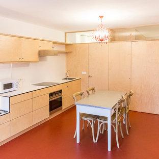 マドリードの中くらいのモダンスタイルのおしゃれなキッチン (アンダーカウンターシンク、フラットパネル扉のキャビネット、淡色木目調キャビネット、珪岩カウンター、白いキッチンパネル、パネルと同色の調理設備、赤い床、白いキッチンカウンター) の写真