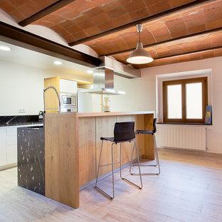 Imagen de cocina lineal, minimalista, con armarios con paneles lisos, puertas de armario blancas, salpicadero negro, electrodomésticos de acero inoxidable, una isla y encimeras negras