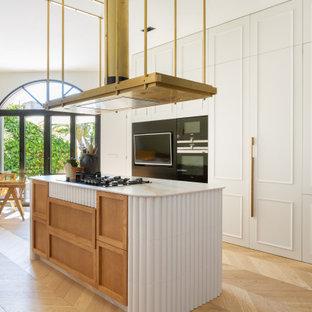 Diseño de cocina comedor de galera, contemporánea, grande, con puertas de armario blancas, encimera de mármol, electrodomésticos negros, suelo de madera clara, una isla, encimeras blancas, armarios con paneles empotrados y suelo beige