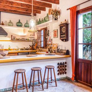 Diseño de cocina en U, mediterránea, con fregadero sobremueble, encimera de azulejos, salpicadero multicolor, península y encimeras multicolor