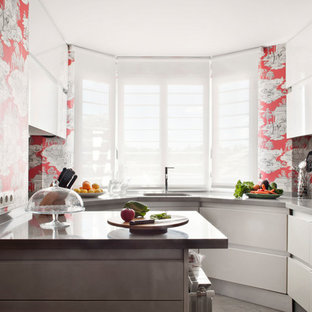 Mid-sized eclectic u-shaped eat-in kitchen in Madrid with flat-panel cabinets, white cabinets, a peninsula, an undermount sink and red splashback.