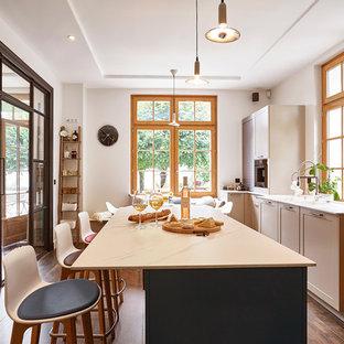 Réalisation d'une cuisine méditerranéenne fermée avec un placard à porte shaker, des portes de placard grises, une crédence en fenêtre, un électroménager de couleur, un sol en bois foncé, un îlot central et un plan de travail blanc.