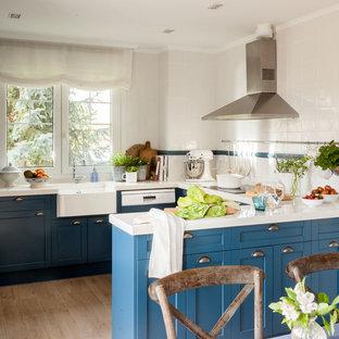 Diseño de cocina comedor en U, clásica renovada, con fregadero sobremueble, armarios estilo shaker, puertas de armario azules, salpicadero blanco, suelo de madera clara, península, suelo marrón y encimeras blancas
