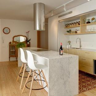 Foto de cocina contemporánea, abierta, con fregadero bajoencimera, armarios con paneles lisos, puertas de armario blancas, encimera de mármol, suelo de madera clara, una isla y encimeras blancas