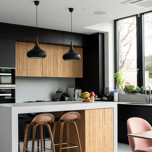 This is an example of a medium sized contemporary l-shaped kitchen/diner in London with flat-panel cabinets, grey splashback, porcelain splashback, concrete flooring, an island, grey floors, grey worktops and medium wood cabinets.