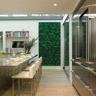 Immagine di una grande cucina minimal con elettrodomestici in acciaio inossidabile, parquet chiaro, isola, ante lisce e ante in acciaio inossidabile