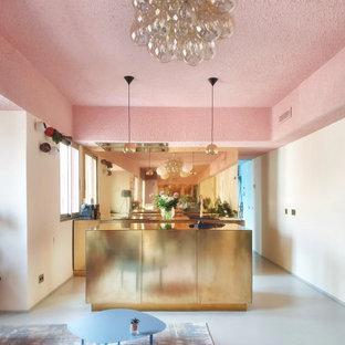 Modelo de cocina de galera, actual, pequeña, abierta, con suelo de cemento, una isla, fregadero encastrado, armarios con paneles lisos, salpicadero metalizado y suelo gris