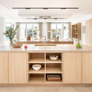 Modelo de cocina en U, contemporánea, de tamaño medio, abierta, con armarios con paneles lisos, puertas de armario de madera clara, electrodomésticos negros, dos o más islas, suelo beige y encimeras beige