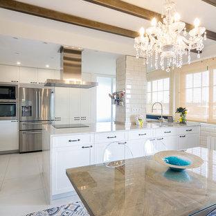 Klassische Wohnküche mit Schrankfronten im Shaker-Stil, weißen Schränken, Küchengeräten aus Edelstahl, Halbinsel, weißer Arbeitsplatte und blauem Boden in Madrid