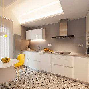 バルセロナの中くらいのモダンスタイルのおしゃれなキッチン (シングルシンク、フラットパネル扉のキャビネット、白いキャビネット、クオーツストーンカウンター、グレーのキッチンパネル、黒い調理設備、セラミックタイルの床、アイランドなし、マルチカラーの床) の写真