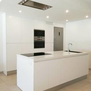 Imagen de cocina lineal, moderna, con armarios con paneles lisos, puertas de armario blancas, electrodomésticos de acero inoxidable, una isla, encimeras blancas, fregadero de un seno y suelo beige
