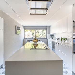 Foto de cocina comedor lineal, contemporánea, grande, con fregadero integrado, armarios con paneles lisos, puertas de armario blancas, salpicadero blanco, electrodomésticos de acero inoxidable y una isla