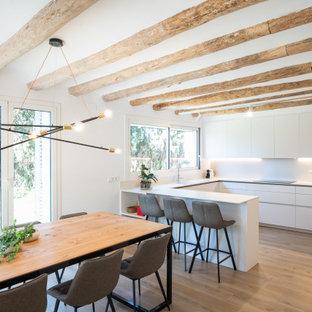 Imagen de cocina en U, actual, con armarios con paneles lisos, puertas de armario blancas, suelo de madera clara, península y suelo beige