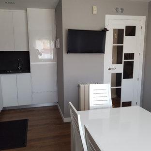 マドリードの小さいモダンスタイルのおしゃれなキッチン (アンダーカウンターシンク、フラットパネル扉のキャビネット、白いキャビネット、亜鉛製カウンター、白いキッチンパネル、トラバーチンのキッチンパネル、シルバーの調理設備、濃色無垢フローリング、アイランドなし、茶色い床、グレーのキッチンカウンター) の写真