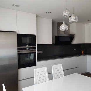 Small modern l-shaped eat-in kitchen in Madrid with an undermount sink, flat-panel cabinets, white cabinets, zinc benchtops, white splashback, travertine splashback, stainless steel appliances, dark hardwood floors, no island, brown floor and grey benchtop.