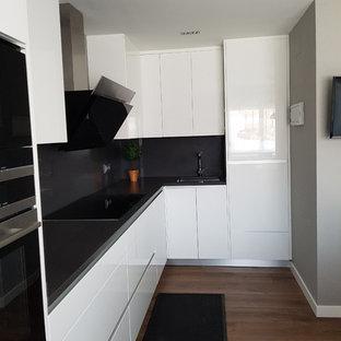 マドリードの小さいモダンスタイルのおしゃれなキッチン (アンダーカウンターシンク、フラットパネル扉のキャビネット、白いキャビネット、亜鉛製カウンター、白いキッチンパネル、トラバーチンの床、シルバーの調理設備の、濃色無垢フローリング、アイランドなし、茶色い床、グレーのキッチンカウンター) の写真