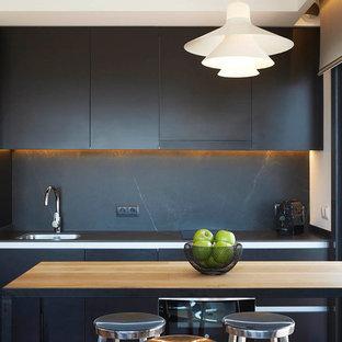 Imagen de cocina lineal, contemporánea, con fregadero encastrado, armarios con paneles lisos, puertas de armario negras, salpicadero negro y una isla