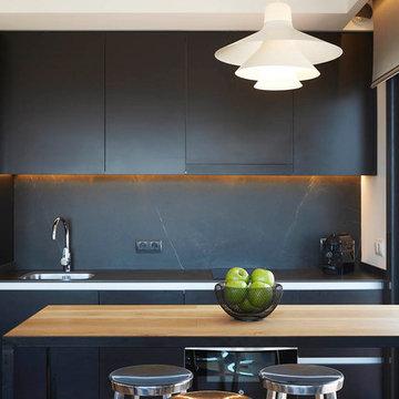 Cocina en color negro con mesa de madera natural - Coblonal Interiorismo