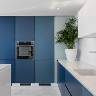 Foto de cocina marinera con fregadero de un seno, armarios con paneles lisos, puertas de armario azules, una isla, suelo blanco y encimeras blancas