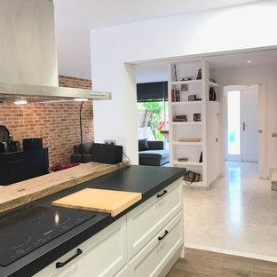 バルセロナの大きいエクレクティックスタイルのおしゃれなキッチン (ダブルシンク、インセット扉のキャビネット、白いキャビネット、御影石カウンター、白いキッチンパネル、セラミックタイルのキッチンパネル、シルバーの調理設備、大理石の床、白い床、黒いキッチンカウンター) の写真