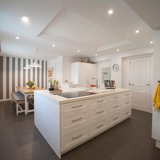 ビルバオの大きい北欧スタイルのおしゃれなキッチン (落し込みパネル扉のキャビネット、白いキャビネット、人工大理石カウンター、シルバーの調理設備の、セラミックタイルの床、白いキッチンカウンター) の写真