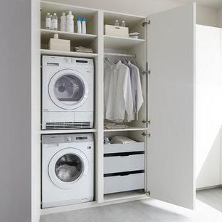 Ejemplo de lavadero minimalista con puertas de armario blancas, paredes blancas y lavadora y secadora apiladas